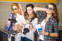 Three young women at the station or at the airport holding a camera, card, a passport, a tablet. Europeans. Gathered in a guided tour. Three friends Royalty Free Stock Image