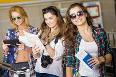 Three young women at the station or at the airport holding a camera, card, a passport, a tablet. Europeans. Stock Photo