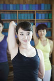 Three young women stretching and doing yoga, looking at camera, Royalty Free Stock Photo