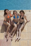 Three young women by the swimming pool Stock Photo