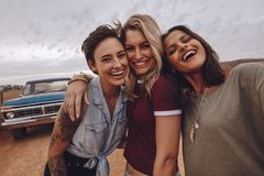 Young women taking self portrait on road trip. Three young women taking self portrait on road trip. Cheerful female friends making selfie with a pickup truck in stock image