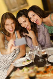 Three young women taking a selfie photo. Three beautiful young women taking a selfie photo in a restaurant Stock Photos