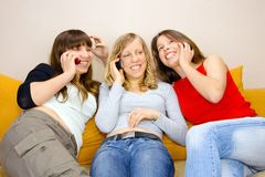 Three Young Women Talking. Three young woman talking by phones while sitting on the sofa Royalty Free Stock Photo