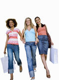 Three young women walking hand in hand with shopping bags, smiling, low angle view, cut out Royalty Free Stock Images