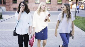 Three young women are walking after work on a summer day stock footage