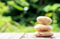 Three zen stones on old wood with nature background Royalty Free Stock Photo