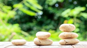 Three zen stones on old wood with nature background Royalty Free Stock Images
