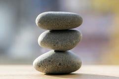 Three zen stones pile, grey meditation pebbles tower. In sunlight royalty free stock image