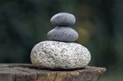 Three zen stones pile on wooden stump, white and grey meditation pebbles tower. Three stones royalty free stock photography