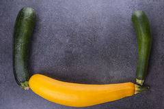 Three zucchini on kitchen table, two green, one yellow royalty free stock photos