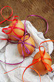 ThreeEaster eggs with bright color tapes on white crumpled paper Royalty Free Stock Images