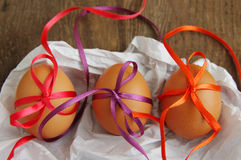 ThreeEaster eggs with bright color tapes on white crumpled paper Royalty Free Stock Photos