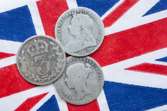 Threepence, silver coin, Victoria. Three Queen Victoria silver threepences from the 19th century (from 1873, 1891, 1898) on a British flag. Concept representing royalty free stock images