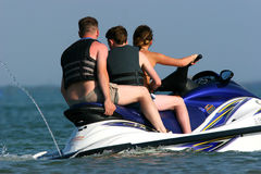Threes A Crowd. Two men and a woman riding together on a blue, white and yellow jet ski stock images