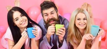 Threesome ослабляет в утре с кофе Любовники в концепции кровати Любовники выпивая кофе в кровати Человек и женщины в отечественно стоковое фото rf