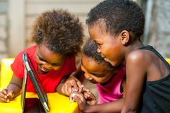 Threesome african kids having fun with tablet. Close up portrait of three african young girls playing together on digital tablet Stock Image