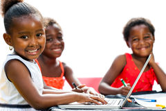Threesome African kids with laptop at table. Portrait of threesome African kids with laptop at table.Isolated on white background Royalty Free Stock Images