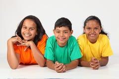 Threesome der glücklichen Schulefreunde, die auf Fußboden liegen Stockbild