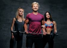 Threesome fitness model of blond and brunette slim women and a m. En holds barbell posing over grey background Royalty Free Stock Photos