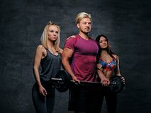 Threesome fitness model of blond and brunette slim women and a m. En holds barbell posing over grey background Stock Photography