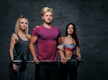 Threesome fitness model of blond and brunette slim women and a m. En holds barbell posing over grey background Stock Photo