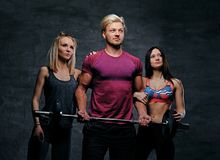 Threesome fitness model of blond and brunette slim women and a m. En holds barbell posing over grey background Stock Image