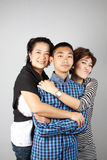 Threesome Funny Hugging. Mother and auntie hugging their straight face teenage boy Stock Photography