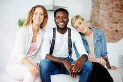 Threesome love. Happy young girls and African-american guy sitting on sofa Stock Photo
