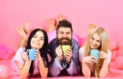 Threesome relax in morning with coffee. Stormy night concept. Man and women, friends on smiling faces lay, pink. Background. Lovers drinking coffee in bed. Man royalty free stock photos