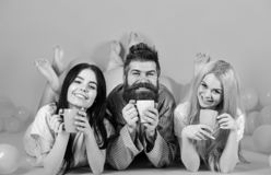 Threesome relax in morning with coffee. Stormy night concept. Man and women, friends on smiling faces lay, pink. Background. Lovers drinking coffee in bed. Man royalty free stock photo