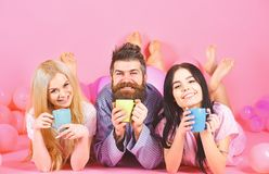 Threesome relax in morning with coffee. Stormy night concept. Man and women, friends on smiling faces lay, pink. Background. Lovers drinking coffee in bed. Man stock photos