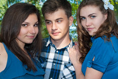 Threesome. Two girls looking in love on one guy outdoor closeup Stock Image