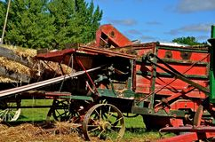 Thresher and Wagon of Shocks in Harvest Mode. An old threshing machine is in the process of separating the grain from stalk and filling the bushel basket Stock Image