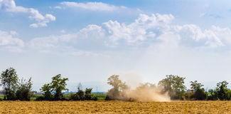 threshing machine in a cloud of dust Stock Image