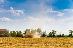 threshing machine in a cloud of dust Stock Photo