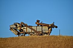 Threshing Machine and Harvest. An old threshing machine sets on a hilltop as a reminder of the old harvest days Stock Image
