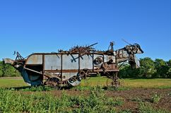 Threshing Machine Left in Pasture. An old vintage threshing machine with parts stored on it's top is left abandoned in a pasture Stock Photos