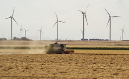 Threshing machine working on a summer field, windmill blade back Royalty Free Stock Photo