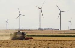 Threshing machine working on a summer field, windmill blade back royalty free stock photo