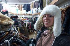 Thrift store shopping 5. Girl with warm winter hat in a thrift store Royalty Free Stock Images