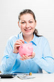 Thrifty woman and piggy pink Royalty Free Stock Photos