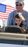The Thrill of Driving. Little girl sitting in her grandfather's lap driving a boat with the american flag blowing in the background Stock Image