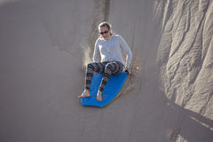 Thrill seeking woman Playing in the Sand Dunes Outdoor Lifestyle. A thrill-seeking adult woman riding a board down a sand dune hill having fun playing outdoors Royalty Free Stock Photo