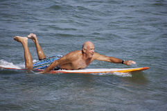 The Thrill of Surfing. Elderly gentleman out surfing on the blue waves stock photography