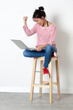 Thrilled beautiful girl sitting on a stool, enjoying her success Royalty Free Stock Photos