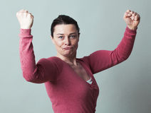 Thrilled beautiful 40s woman flexing her muscles up Royalty Free Stock Photos