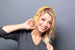 Thrilled blond woman listening to music on headphones Stock Image