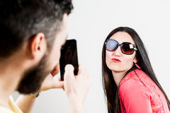 Thrilled couple taking mobile photographs and selfies Stock Photo