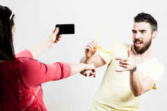 Thrilled couple taking mobile photographs and selfies Stock Image