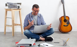 Thrilled creative entrepreneur sitting on floor to relax and work Stock Images